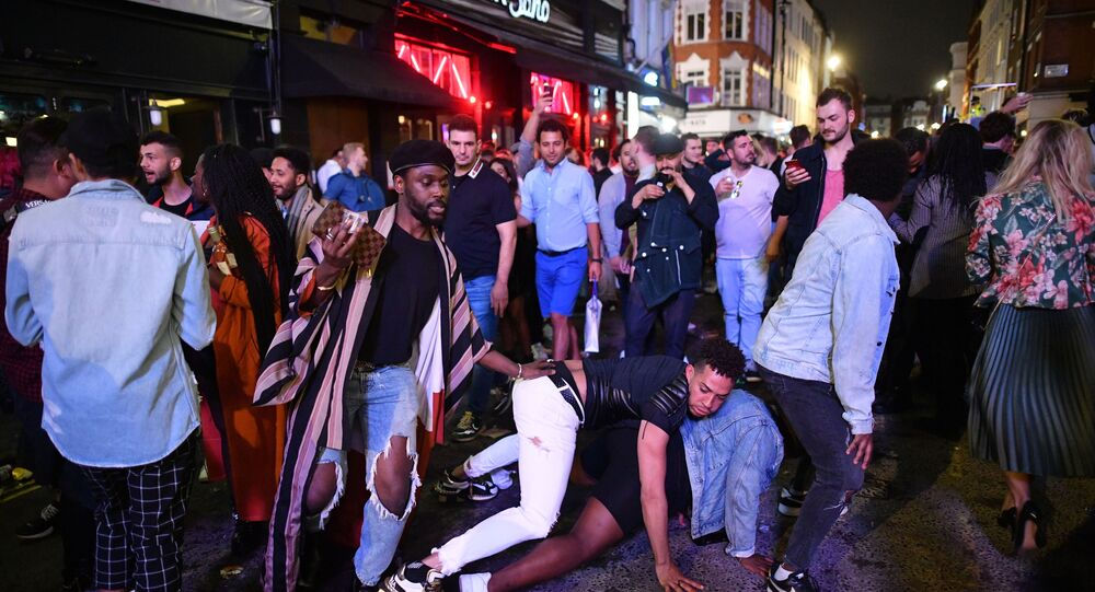 Revellers dance in the street in the Soho area of London on July 4, 2020, following a further easing of restrictions to allow pubs and restaurants to open during the novel coronavirus COVID-19 pandemic.