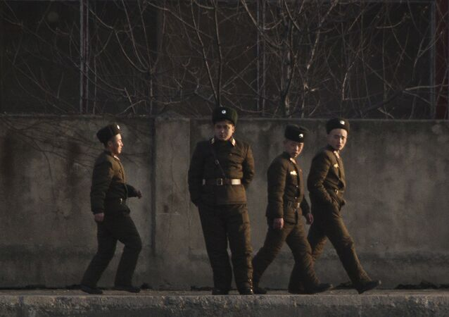 North Korean soldiers walk along the river bank of the North Korean town of Sinuiju, opposite side to the Chinese border city of Dandong, Tuesday, Dec. 20, 2011