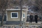 North Korean soldiers look as they stand guard along the river bank of the North Korean town of Sinuiju, opposite side to the Chinese border city of Dandong, Tuesday, Dec. 20, 2011