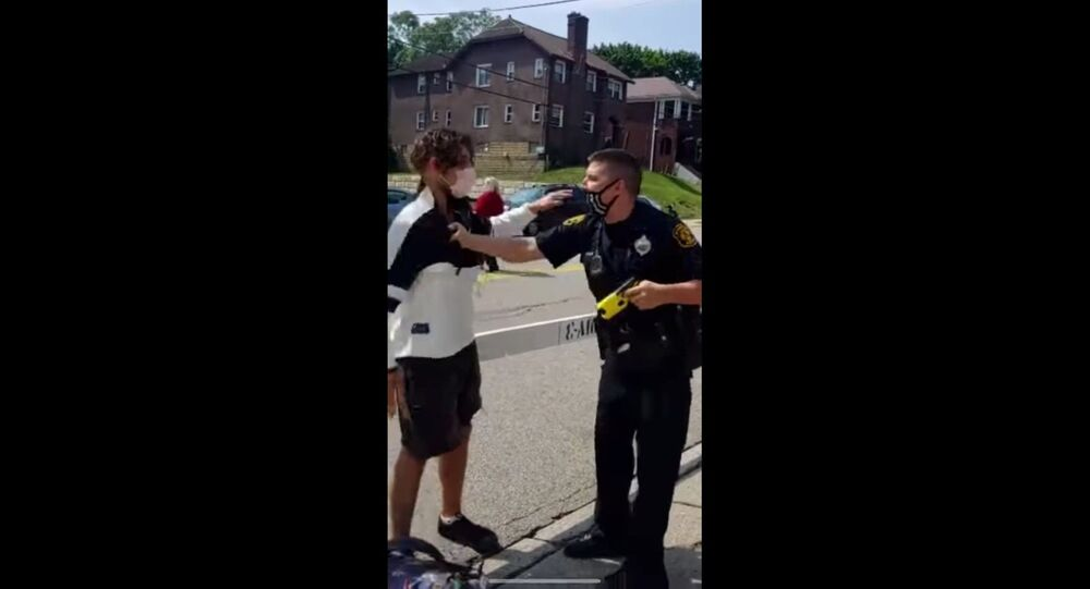 Screenshot captures moment in which an officer with Pennsylvania's Pittsburgh Bureau of Police placed a local resident under arrest for questioning his choice of face mask. At the time the officer was sporting a mask that was designed with the American flag; however, it was embroidered with a blue line - an image used as part of a pro-police movement in response to the Black Lives Matter movement.