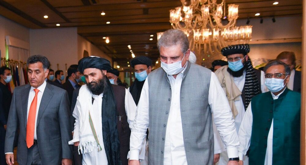 Pakistan's Foreign Minister Shah Mahmood Qureshi walks with Mullah Abdul Ghani Baradar (2nd L), the leader of the Taliban delegation, upon his arrival at the Ministry of Foreign Affairs (MOFA) office in Islamabad, Pakistan August 25, 2020.
