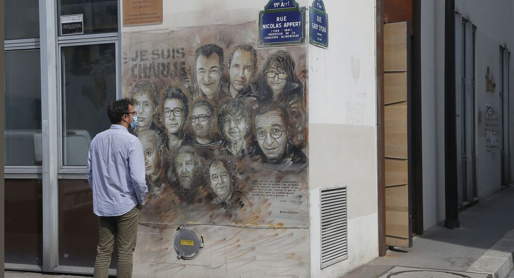 A man wearing a protective face mask as a precaution against the coronavirus looks on a painting by French street artist Christian Guemy, a.k.a. 'C215' in Paris Wednesday, Sept. 2, 2020, in tribute to the members of the satirical newspaper Charlie Hebdo attack by jihadist gunmen in January 2015. Thirteen men and a woman go on trial Wednesday over the 2015 attacks against a satirical newspaper and a kosher supermarket in Paris that marked the beginning of a wave of violence by the Islamic State group in Europe. Seventeen people and all three gunmen died during the three days of attacks in January 2015