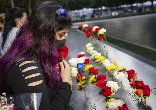 A mourner kisses a rose through her face mask before placing it in a name cut-out of the deceased at the National September 11 Memorial and Museum, Friday, Sept. 11, 2020, in New York