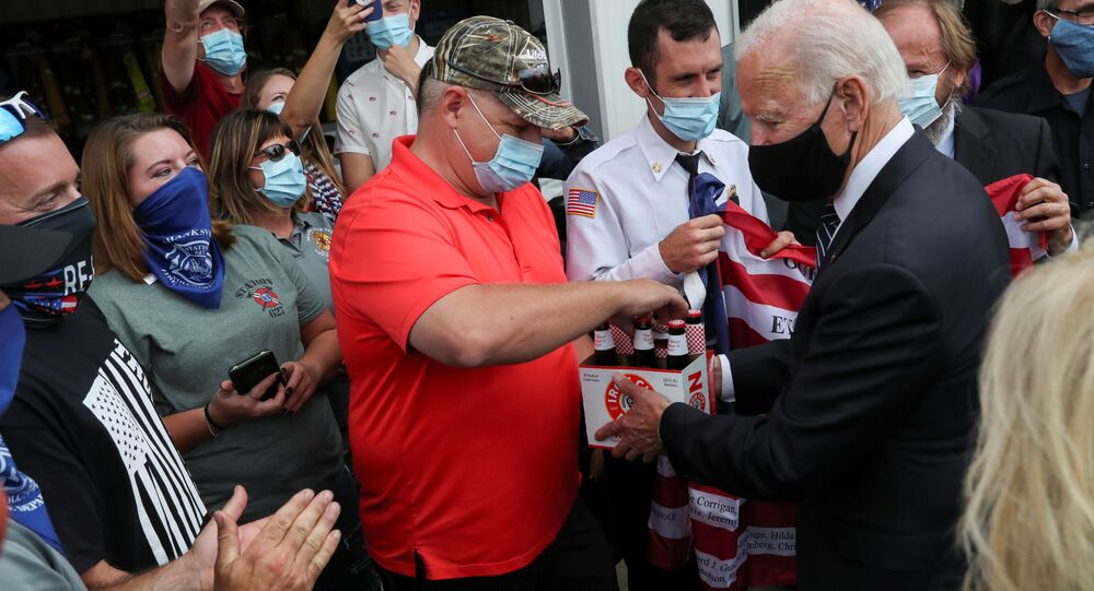 Democratic U.S. presidential nominee and former Vice President Joe Biden hands over a six pack of beer to Frank Barta that he said he brought for firefighters after promising to bring beer during a previous visit to Shanksville fire station number 627 long ago, as Biden stopped at the fire hall after visiting the nearby Flight 93 National Memorial to those killed when hijacked Flight 93 crashed into an open field on September 11, 2001, in Shanksville, Pennsylvania, September 11, 2020.