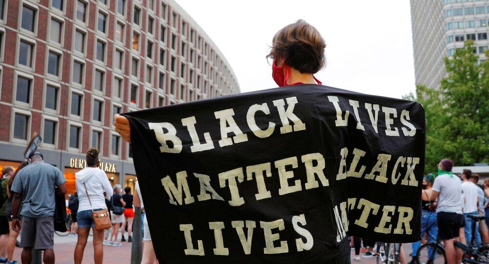 A demonstrator holds a Black Lives Matter banner