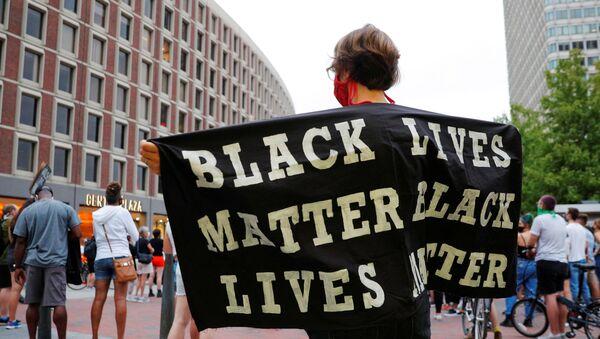 A demonstrator holds a Black Lives Matter banner  - Sputnik International