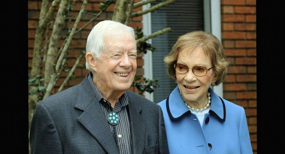 In this image from video, former President Jimmy Carter and former first lady Rosalynn Carter, seen in a photo as they speak on audio only, during the second night of the Democratic National Convention on Tuesday, Aug. 18, 2020.