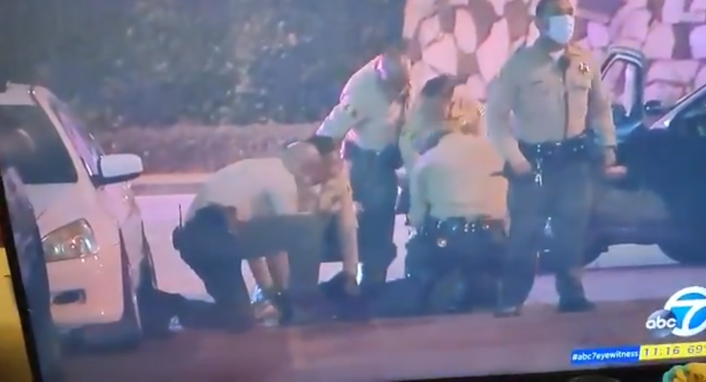 Screenshot from an ABC TV report revealing police officers detaining a reporter during protests in Los Angeles