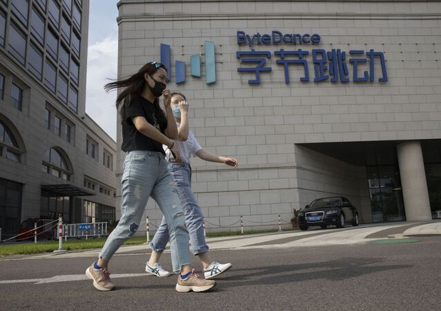 Women wearing masks to prevent the spread of the coronavirus chat as they pass by the ByteDance headquarters in Beijing, China on Friday, Aug. 7, 2020. President Donald Trump on Thursday ordered a sweeping but unspecified ban on dealings with the Chinese owners of consumer apps TikTok and WeChat, although it remains unclear if he has the legal authority to actually ban the apps from the U.S. TikTok is owned by Chinese company ByteDance