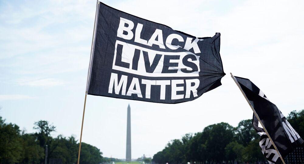 A demonstrator holds a BLM flag during a Get Your Knee Off Our Necks march in front of the Lincoln Memorial in support of racial justice that is expected to gather protestors from all over the country in Washington, U.S., August 28, 2020.