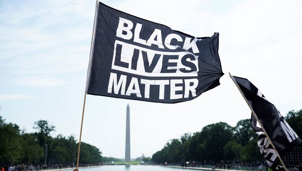 A demonstrator holds a BLM flag during a Get Your Knee Off Our Necks march in front of the Lincoln Memorial in support of racial justice that is expected to gather protestors from all over the country in Washington, U.S., August 28, 2020.  - Sputnik International