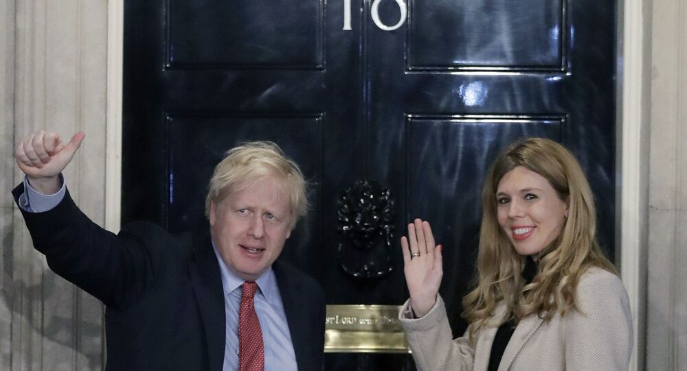 FILE -In this Friday, Dec. 13, 2019 file photo, Britain's Prime Minister Boris Johnson and his partner Carrie Symonds wave from the steps of number 10 Downing Street in London.