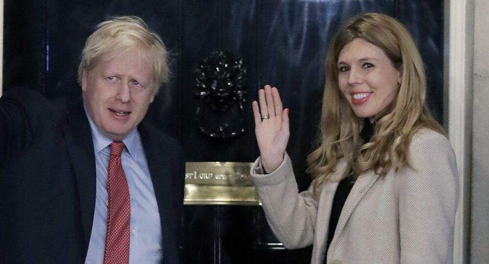 In this Friday, 13 December 2019 file photo, Britain's Prime Minister Boris Johnson and his partner Carrie Symonds wave from the steps of number 10 Downing Street in London.