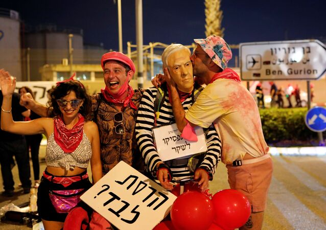 Israelis take part in a demonstration against Israeli Prime Minister Benjamin Netanyahu before his flight to the US to sign an accord with the UAE, near Ben Gurion International Airport, 13 September 2020. The placard in Hebrew reads  Did you destroy it alone?