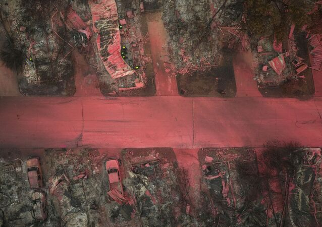 A search and rescue team, surrounded by red fire retardant, look for victims under burned residences and vehicles in the aftermath of the Almeda fire in Talent, Oregon, U.S., September 13, 2020