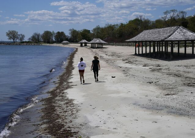 Women walk  along the beach on the Long Island Sound on Tod's Point in Old Greenwich, Connecticut on May 7, 2020.