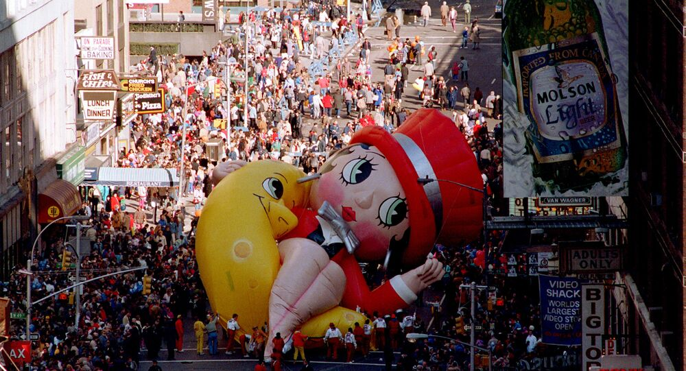 Betty Boop collapses on Broadway near 49th Street as handlers work to raise the deflated helium balloon during the Macy's Thanksgiving Day Parade in New York City, Thursday, Nov. 27, 1986.  Betty Boop, the last balloon in the parade, could not finish the parade.  (AP Photo/Ron Frehm)