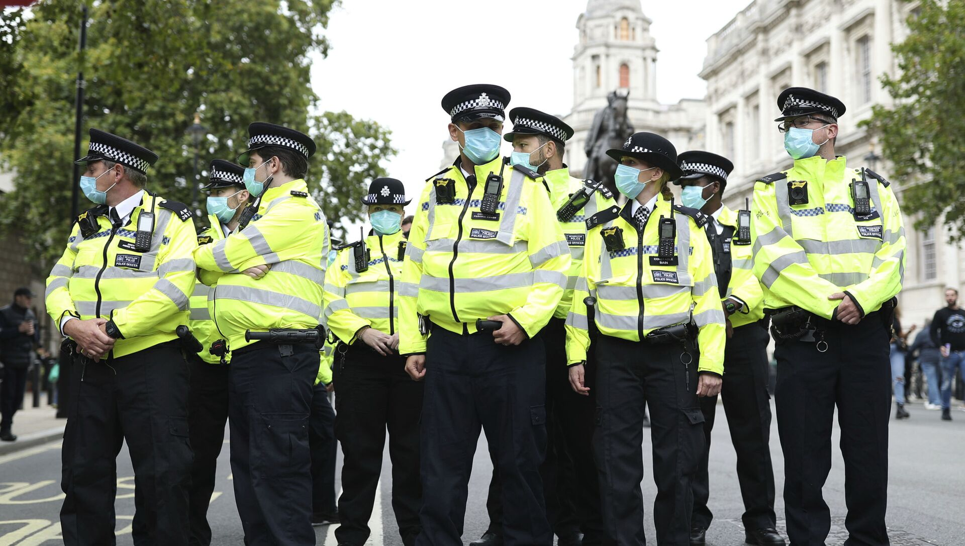 Police officers wearing face masks stand guard during a protest opposed to COVID-19 pandemic restrictions, in Trafalgar Square, London, 29 August, 2020 - Sputnik International, 1920, 27.07.2021