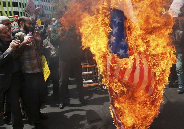 Iranian protestors burn a likeness of a U.S. flag during a gathering after their Friday prayer in Tehran, Iran, 11 May 2018
