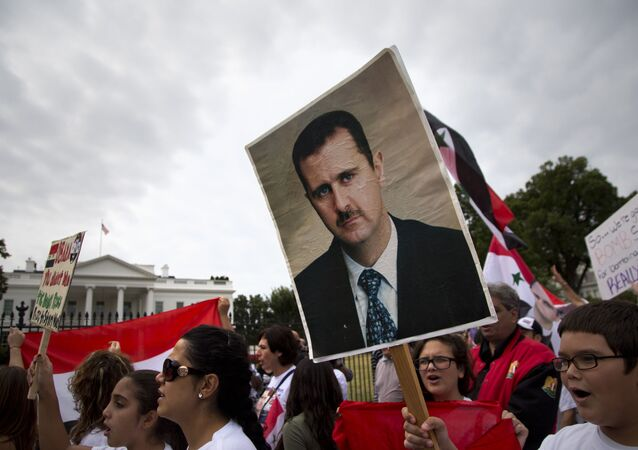 Protesters carry an image of Syrian President Bashar Hafez al-Assad during a demonstration against US military action in Syria, Monday, Sept. 9, 2013, in front of the White House in Washington. On Tuesday, President Barack Obama will address the nation regarding Syria