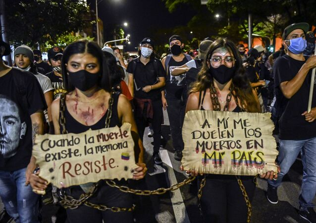 "Women hold signs reading ""When death exists, memory resists"" and ""The dead on my country hurt me"" during a protest against police brutality in Medellin, Colombia, on September 14, 2020. - At least 10 people were killed and hundreds wounded after rioting broke out in the Colombian capital Bogota during a protest to demand justice for victims of police brutality, after the recent death of Javier Ordonez while in custody."