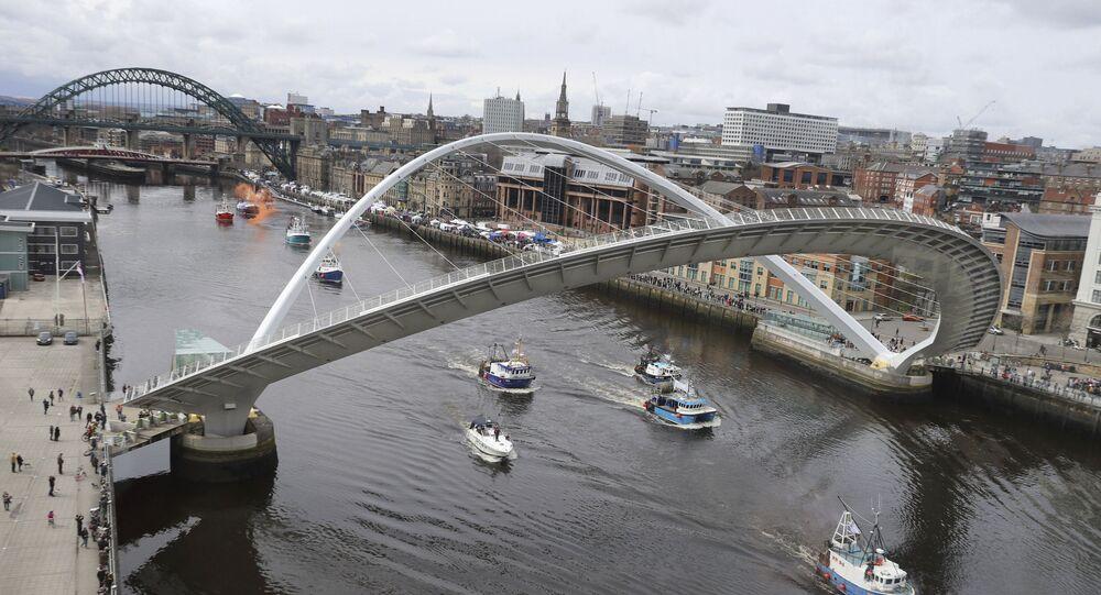 A flotilla of fishing boats sail by the Gateshead Millennium bridge
