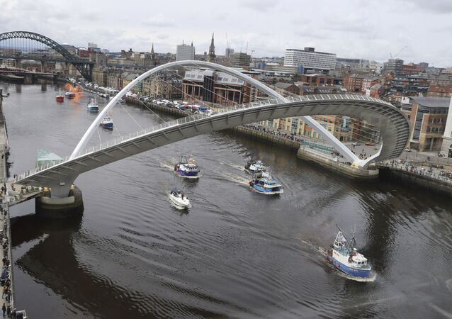 A flotilla of fishing boats sail by the Gateshead Millennium bridge