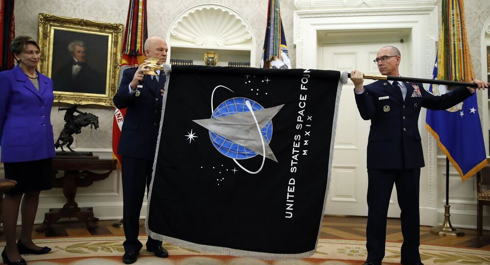 Chief of Space Operations at US Space Force Gen. John Raymond, center, and Chief Master Sgt. Roger Towberman, right, hold the United States Space Force flagas it is presented in the Oval Office of the White House, Friday, May 15, 2020, in Washington.  Secretary of the Air Force Barbara Barrett stands far left.