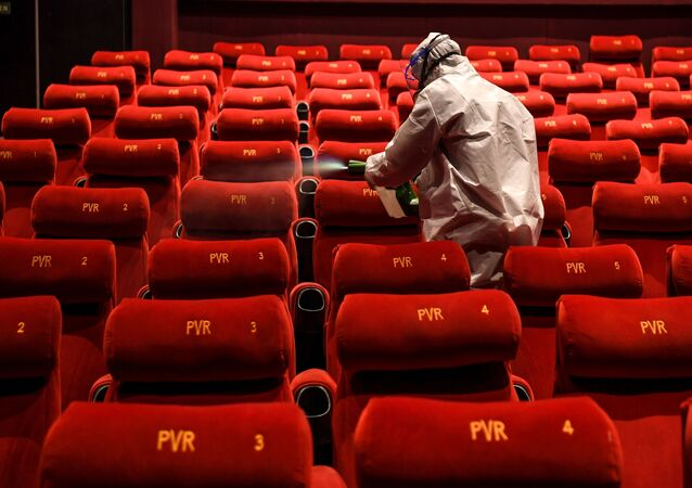 A PVR Cinemas employee wearing a Personal Protective Equipment (PPE) suit sanitises a cinema hall as part of preparations for a possible reopening amid concerns over the spread of the COVID-19 coronavirus, in New Delhi on July 31, 2020.
