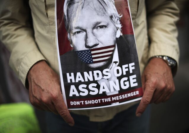 A man holds a photograph of WikiLeaks founder Julian Assange during a protest demanding the freedom of Assange in front of the UK embassy in Brussels, Monday, Sept. 7, 2020