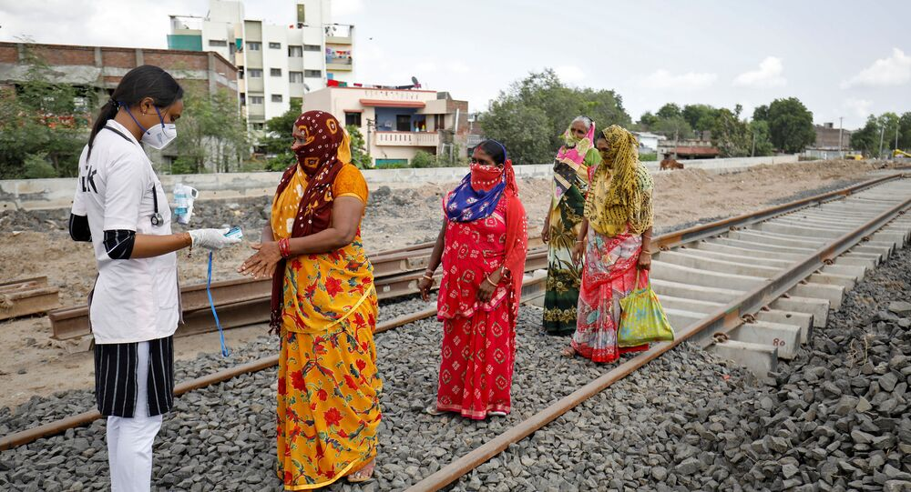 A healthcare worker puts a pulse oximeter on a woman's finger to check her oxygen level during survey for the coronavirus disease (COVID-19) at the construction site of a railway track, amidst the spread of the disease in Babla village on the outskirts of Ahmedabad, India, 15 September 2020