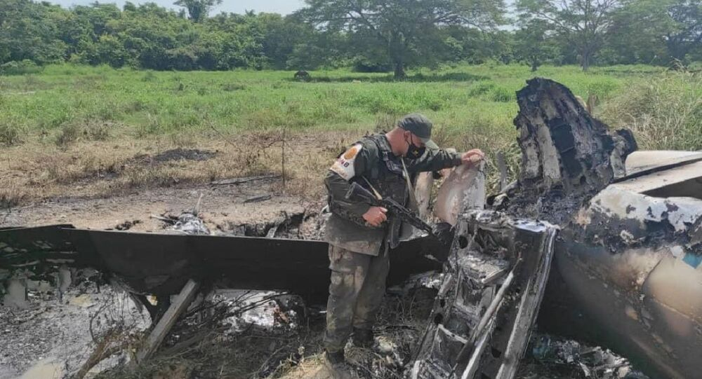 Venezuelan military officials inspect downed US-registered jet allegedly used to smuggle drugs.