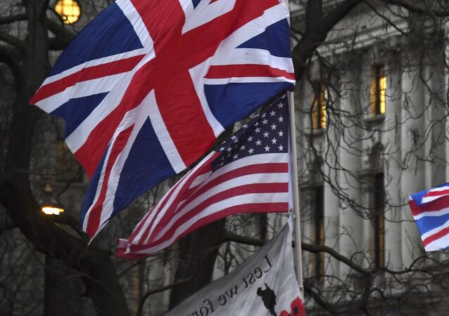 In this file photo dated Friday, Jan. 31, 2020, Brexit supporters hold British and US flags during a rally in London
