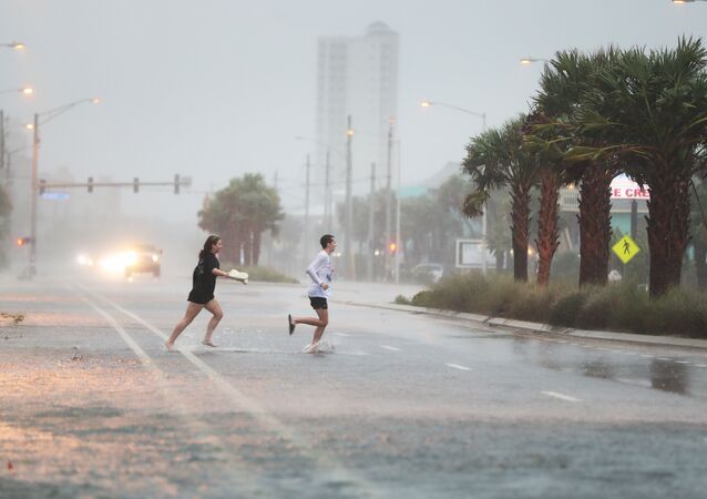 People run across a road through the rain and wind as the outer bands of Hurricane Sally come ashore on September 15, 2020 in Gulf Shores, Alabama