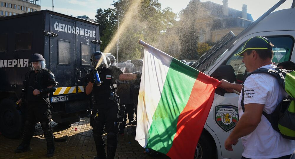 Police use pepper spray in front of a man holding a Bulgarian national flag as clashes errupt during an anti-government demonstration in Sofia as Parliament discusses changing constitution on September 2, 2020.