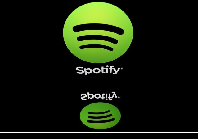 This combination created on March 13, 2019 of file illustrations displayed on tablet screens shows the logo of the US multinational technology company Apple (bottom, February 18, 2019 in Paris) and the logo of online streaming music service Spotify (April 19, 2018 in Paris). - Swedish music streaming giant Spotify said on March 13, 2019 it had filed a formal complaint with the EU Commission against Apple, accusing its US rival of stifling competition in the online music market.