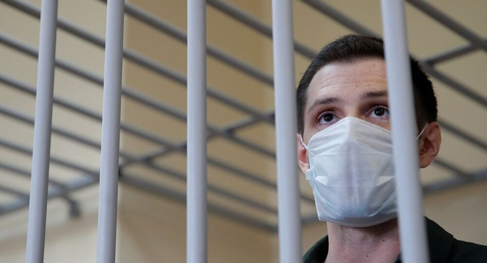 Former U.S. Marine Trevor Reed, who was detained in 2019 and accused of assaulting police officers, stands inside a defendants' cage during a court hearing in Moscow, Russia July 30, 2020.