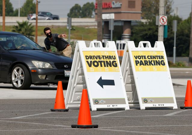 A worker directs a vehicle during a media preview of a new major vote center that will begin operation October 30th at the Honda Center in Anaheim, California, U.S., September 16, 2020