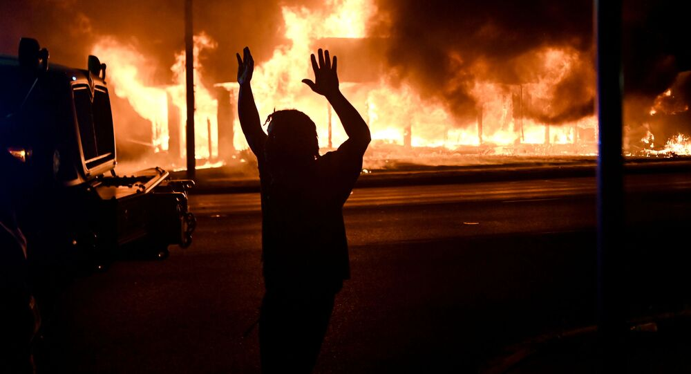 A man walks by an armoured vehicle as B&L Office Furniture burns in the background as protests turn to fires after a Black man, identified as Jacob Blake, was shot several times by police last night in Kenosha, Wisconsin, U.S. August 24, 2020. Picture taken August 24, 2020.