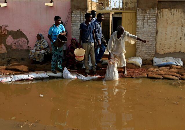 Residents pour out the waters of the Blue Nile floods from their backyard within the Al-Ikmayr area of Omdurman in Khartoum, Sudan August 27, 2020.