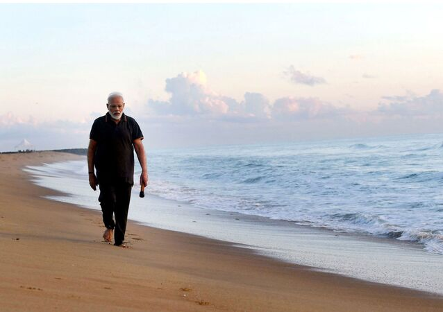In this photo provided by Prime Minister of India Narendra Modi's twitter handle, Indian Prime Minister Narendra Modi takes morning walk at a beach in Mamallapuram, in southern India, Saturday, Oct. 12, 2019