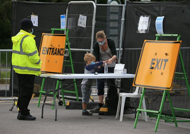 People wearing a face coverings due to the COVID-19 pandemic, sanitise their hands as they arrive at a novel coronavirus testing centre in Stockport, northwest England on September 16, 2020.