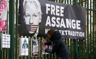 A supporter of WikiLeaks founder Julian Assange posts a sign on the Woolwich Crown Court fence, ahead of a hearing to decide whether Assange should be extradited to the United States, in London, Britain February 25, 2020