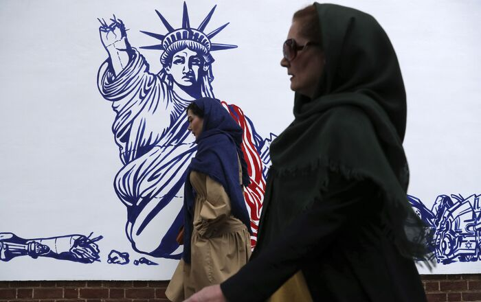 People walk past a satirical drawing of Statue of Liberty after new anti-U.S. murals on the walls of former U.S. embassy unveiled in a ceremony in Tehran, Iran, Saturday, Nov. 2, 2019