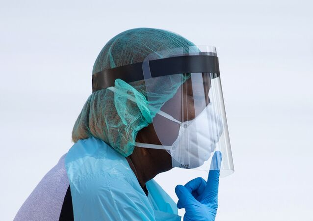 A healthcare worker points to her mask, while requesting a resident to lower their mask to their mouth, at a coronavirus disease (COVID-19) drive in testing location in Houston, Texas, U.S., August 18, 2020.
