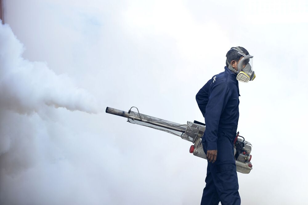 A municipal worker fumigates an area to kill off mosquitos inside the Lumbini school in Colombo on 15 September 2020.