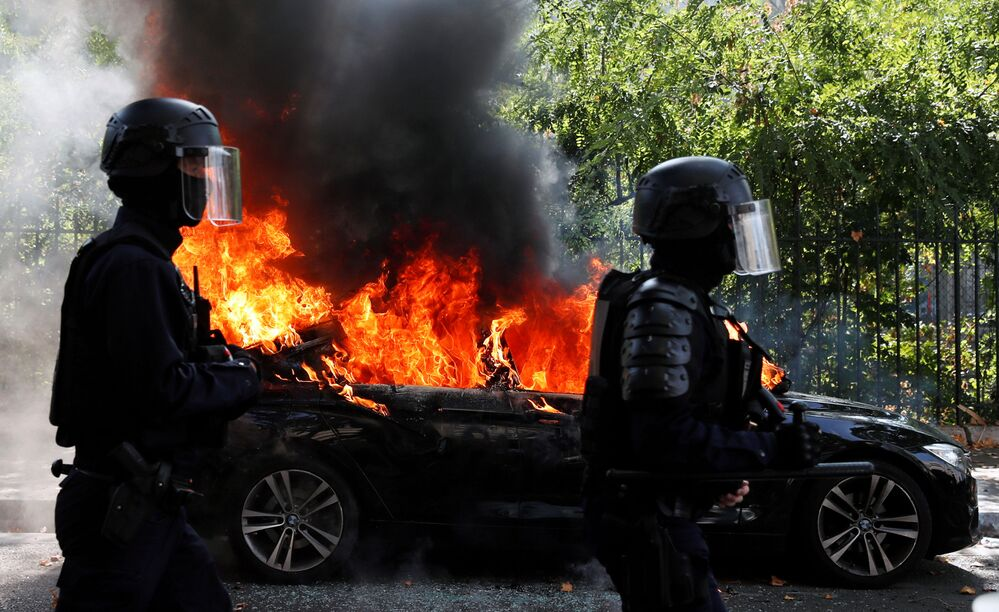 French CRS riot police officers walk past a burning car during a demonstration of the yellow vests movement in Paris, France 12 September 2020.