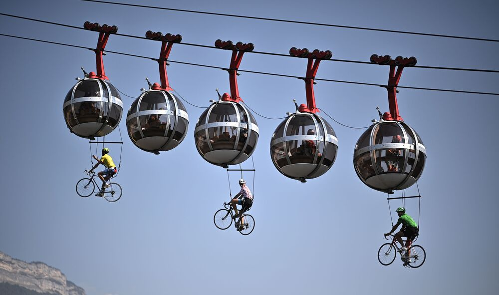 This picture shows cyclists hanging under the Grenoble Bastille cable cars during the 17th stage of the 107th edition of the Tour de France cycling race, 170 km between Grenoble and Meribel, on 16 September 2020.
