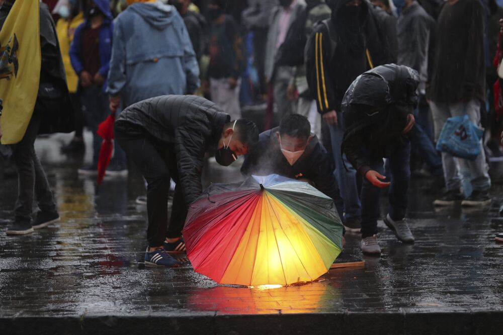 Demonstrators try to keep torches lit under an umbrella during a protest to reject the government's economic policies, rising unemployment and the signing of an agreement with the International Monetary Fund, in Quito, Ecuador, Wednesday, 16 September 2020.