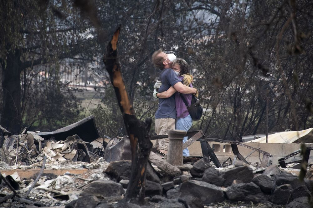 Dee Perez comforts Michael Reynolds in the ruins of his home destroyed in the Almeda Fire in Talent, Oregon, 15 September  2020.  Infernos across California, Oregon and Washington state have burned more than five million acres (two million hectares) this year, killed dozens of people and forced hundreds of thousands from their homes.